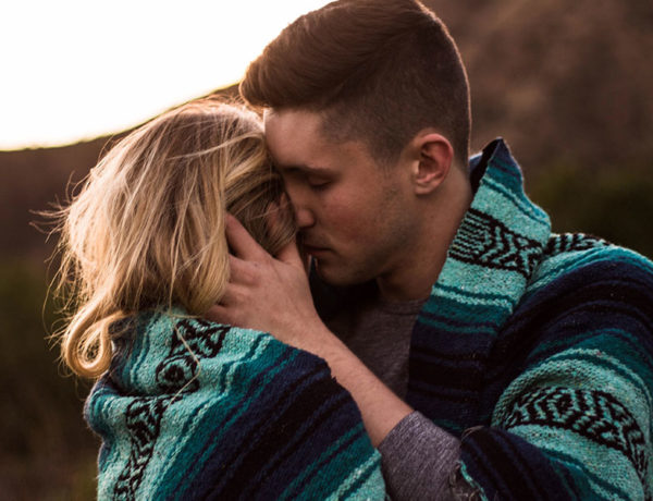 A couple of hopeless romantic people kissing at sunset while wrapped in a blanket.