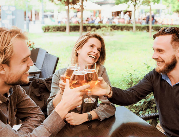 A couple who follows their own set of open relationship rules cheersing drinks with another friend at the bar.