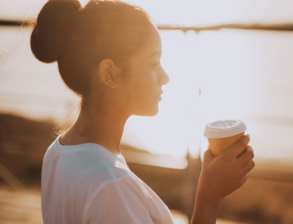 "A girl wondering, ""Should I break up with my boyfriend"" while sipping coffee and watching the sunrise."