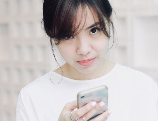 A girl making an annoyed face at her phone as she prepares to respond to breadcrumbing messages.