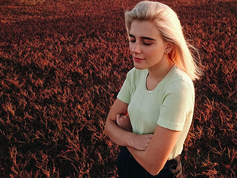 A woman hugging herself in a field and thinking after learning how to move on after being cheated on.