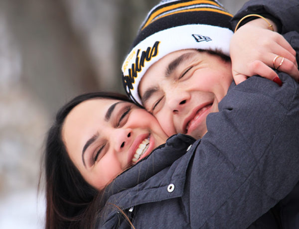 A woman and her boyfriend who learned these dating tips by living through them hugging and smiling like a couple of goof balls.