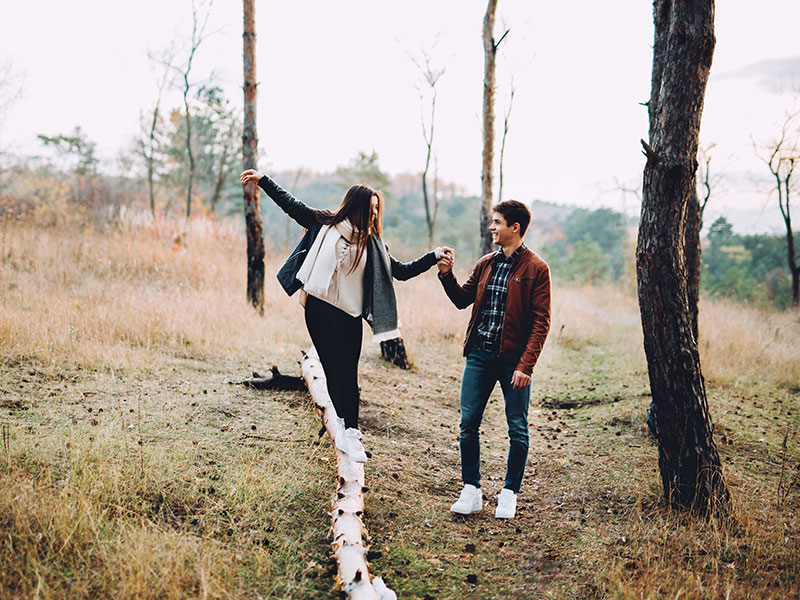 "A girl who's wondering ""is he thinking about me?"" balancing on a log while the guy she likes helps her and looks on with a smile."