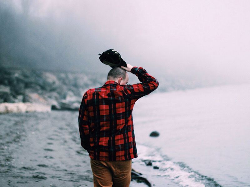 An emotionally unavailable man walking down a foggy beach and thinking.
