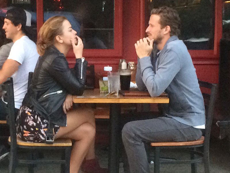 A couple calmly having an argument at a coffee shop.
