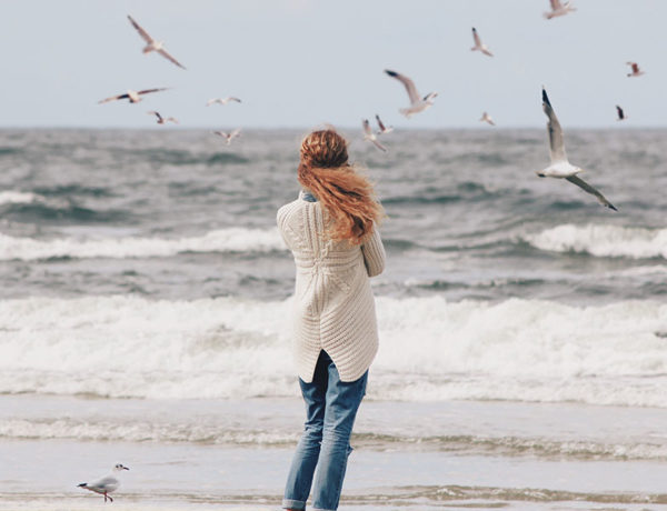 A woman who's wondering why her boyfriend is acting weird, standing on the beach alone and wondering.