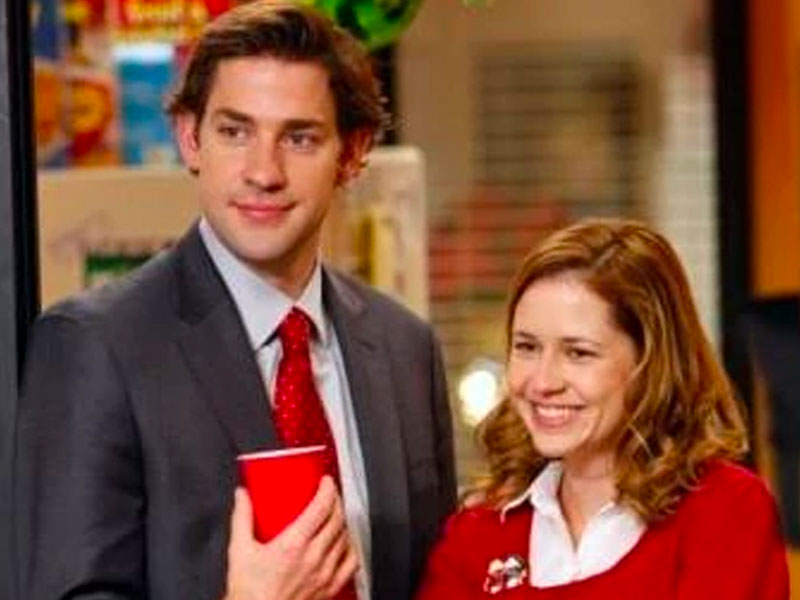 Jim and Pam from the office laughing in the corner of a room.