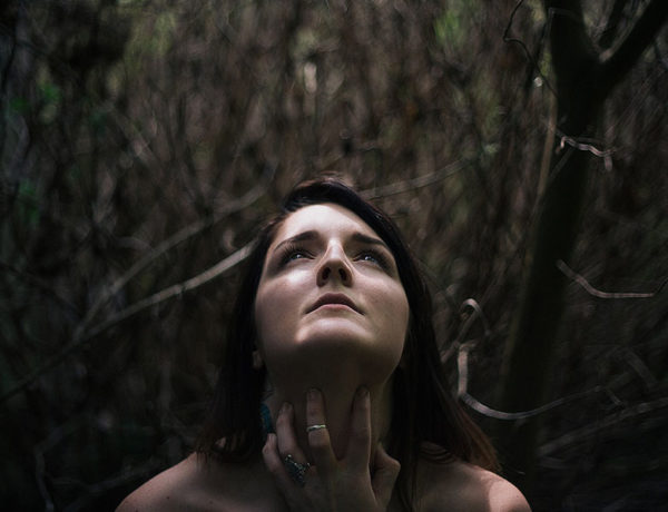 A woman who's experienced gaslighting, trying to make sense of her experience while standing in the woods.