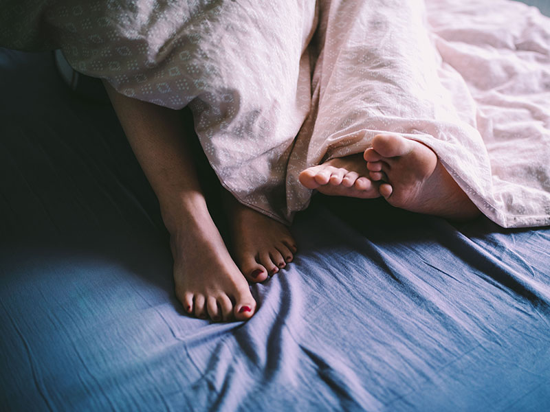A couple's feet sticking out of the sheets after they had first date sex.