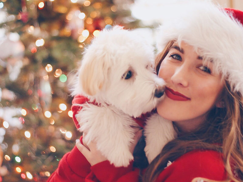 A woman in her 40s, hugging her dog in front of her Christmas tree.