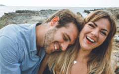 A woman who learned about the body language of men, laughing with her boyfriend as he leans on her.