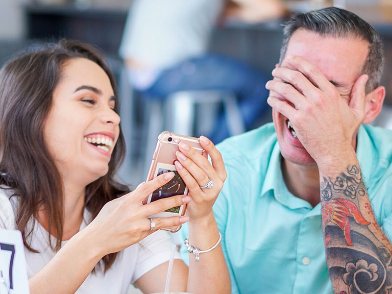 A couple laughing while looking at their phone after meeting on one of the best online dating sites.