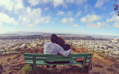 A couple who took these mature dating tips, sitting on a bench and looking at the city view.