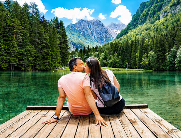 A woman dating an older man, kissing him on a dock in front of a beautiful mountain.