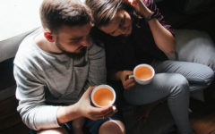 "A woman wondering ""Do I love him?"" as she cuddles up with her boyfriend as they drink tea."