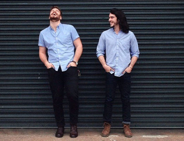 Two men who are life partners standing against a wall and laughing together in their engagement photos.