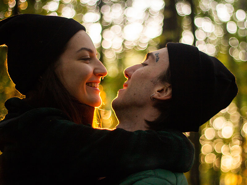 A couple who's good at emotional engagement, hugging and smiling at each other in the woods.