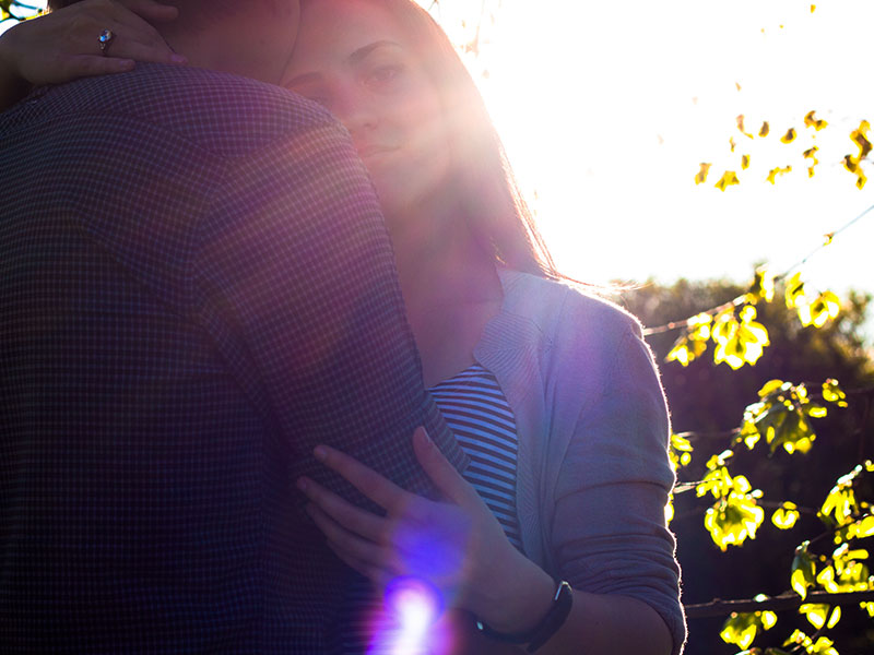 A woman who learned how to make up after a fight, hugging her boyfriend in the sun and reflecting.