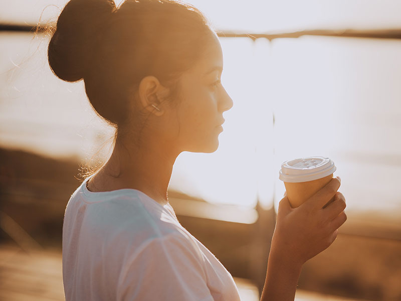 A woman with a fear of relationships after divorce drinking coffee and watching the sunrise.