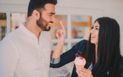 A happy couple in a committed relationship flirting as the woman puts ice cream on her boyfriend's nose.