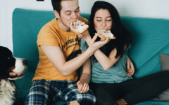 A guy who learned how to flirt with a girl, feeding a girl pizza as she laughs and takes a bite.