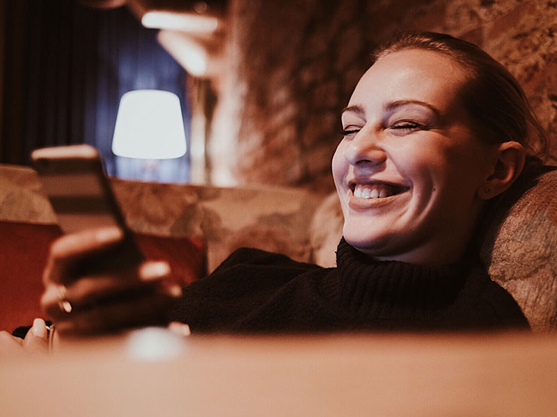A Tinder woman on the Tinder dating app laughing as she's at home drinking wine.