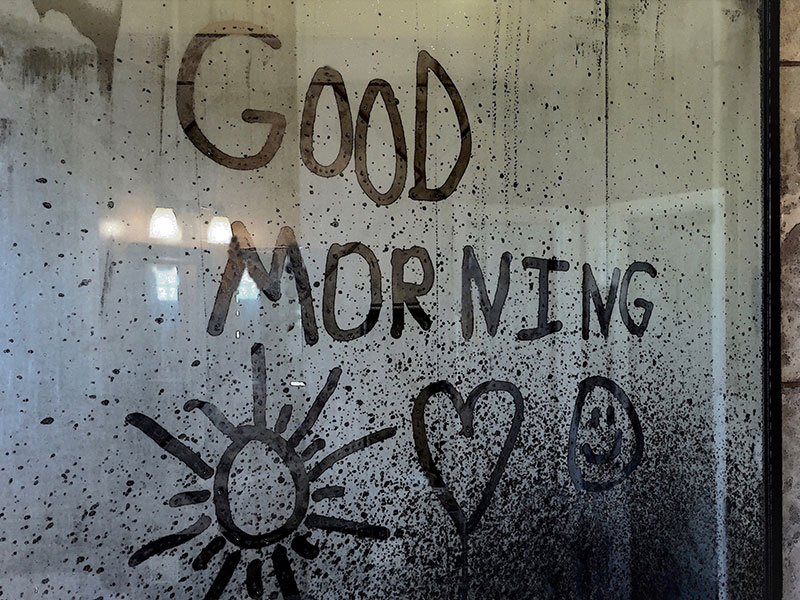 A message written on a rainy window that says good morning from a man who learned how to be romantic.