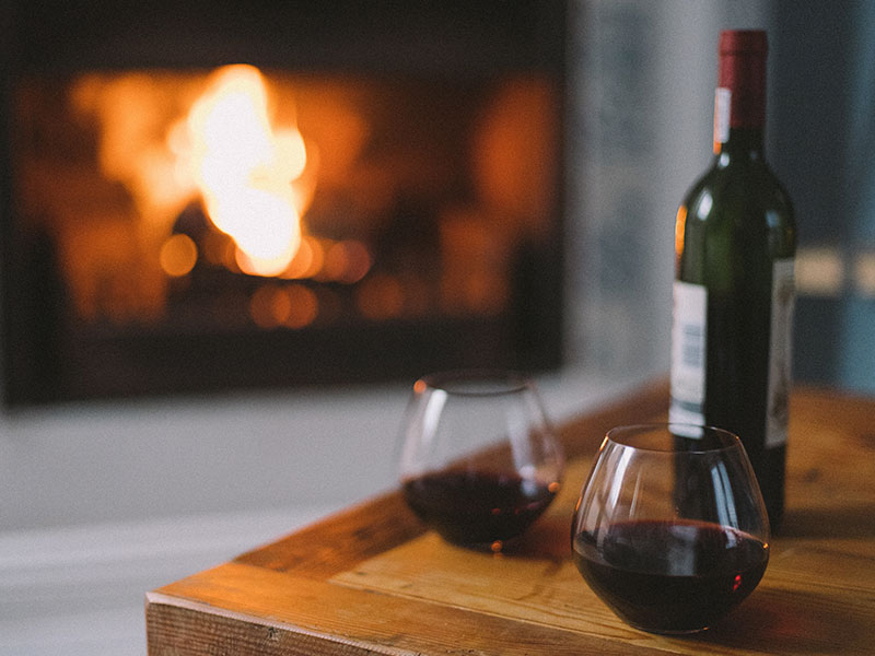 A fireplace and wine and two glasses sitting out on a couple's third date.
