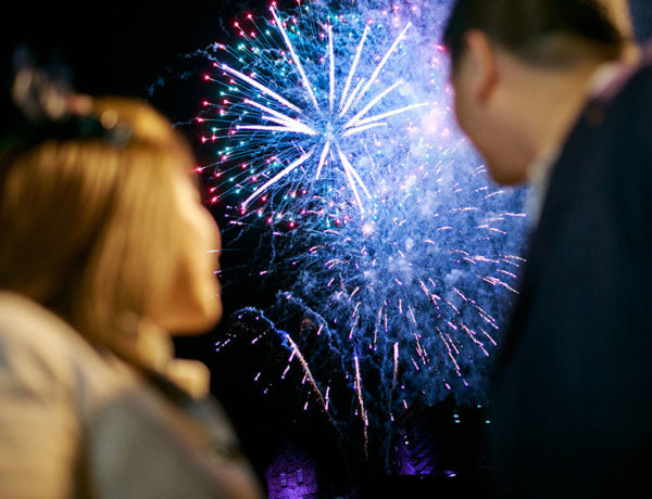 A couple who made New Year's resolutions for dating looking at fireworks going off and feeling hopeful.