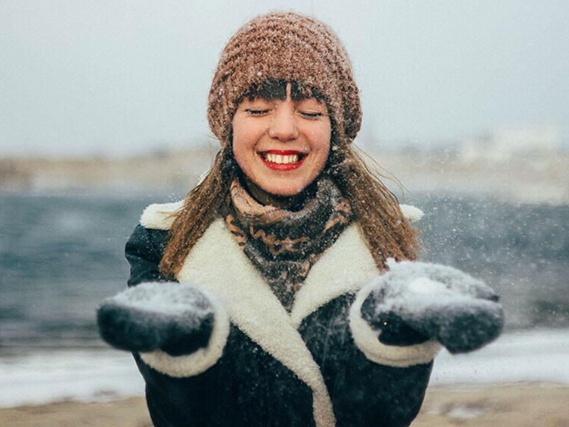 A woman who's learned how to stop attracting players, smiling as she plays in the snow and let's it fall on her.