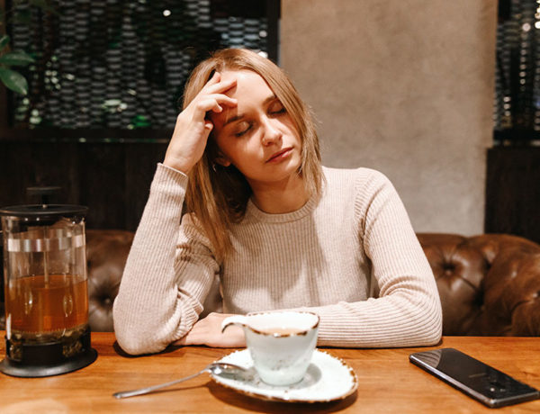 A woman who's getting the silent treatment abuse from her partner looking upset and stressed out at the dinner table.