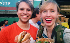 Two people who wanted to meet people offline, eating chicken sandwiches at a baseball game.