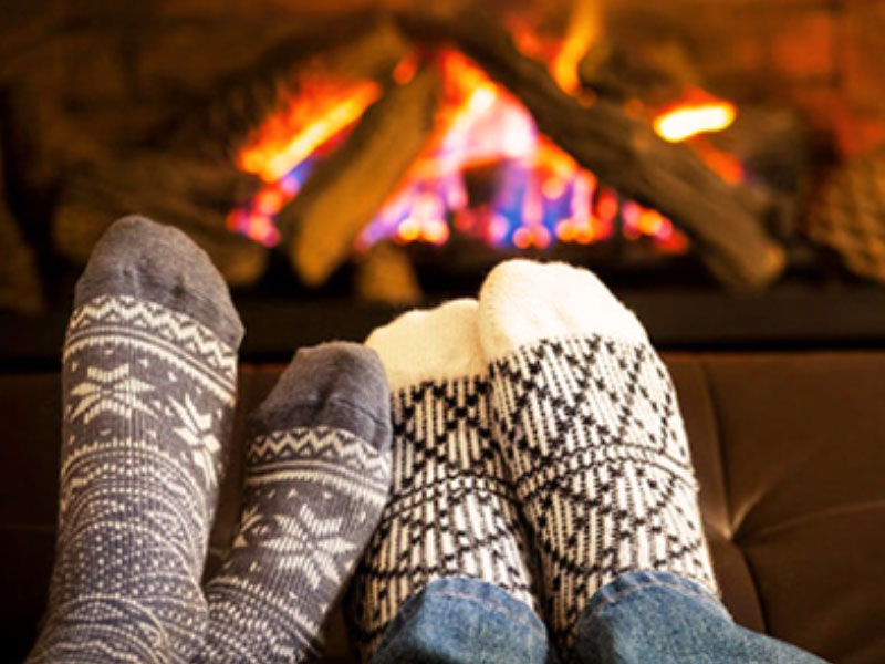 A couple who took one of these winer date ideas and are snuggling up in front of the fire.