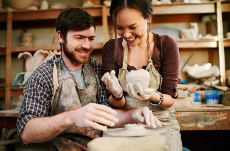 A couple laughing while making cookies at a class, one of the best winter date ideas.