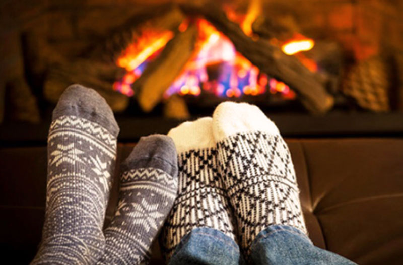 A couple by the fire snuggled up and having a great time on this winter date ideas.