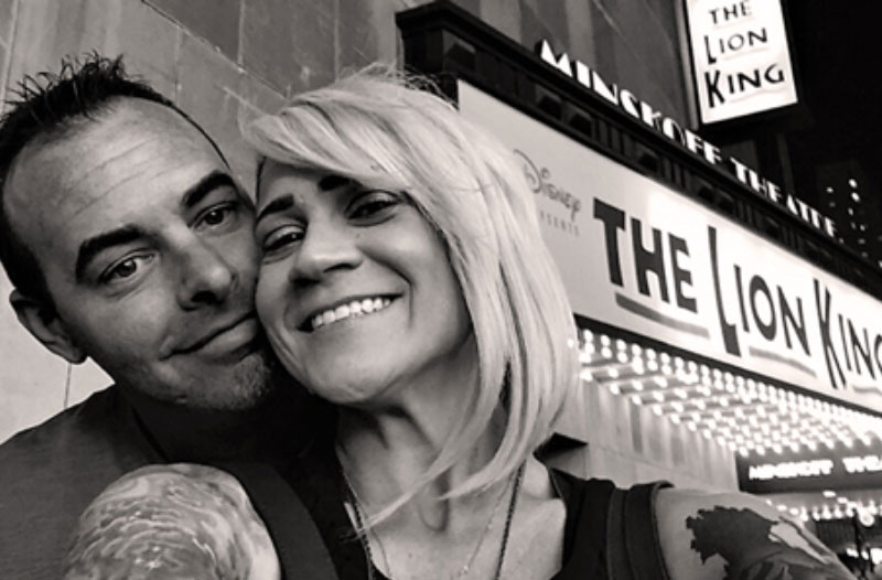 A couple smiling in front of a theatre because they took advantage of this winter date ida.