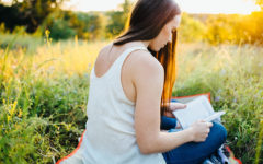 A woman getting over a crush, reading her journal in a field.