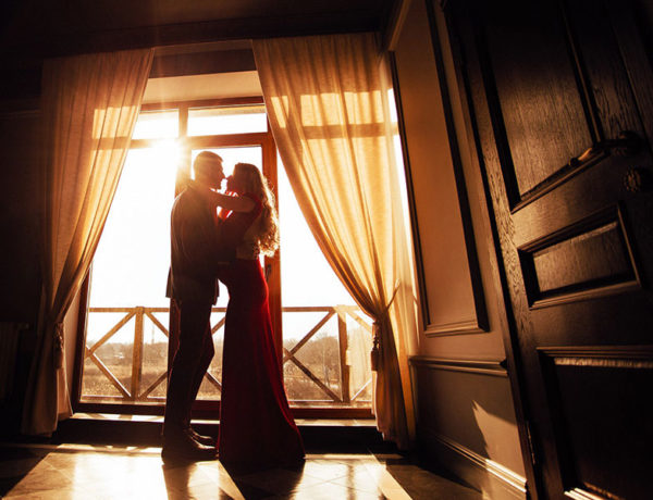 Two hopeless romantics kissing in front of a window at sunset.