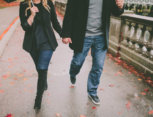 A couple using one of these rainy day date ideas, running through the rain while holding hands.