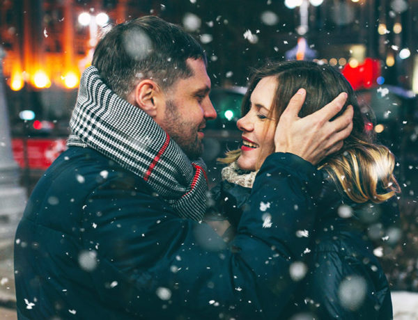 A guy experiencing blind love, kissing his date in the snow as they both smile at each other.