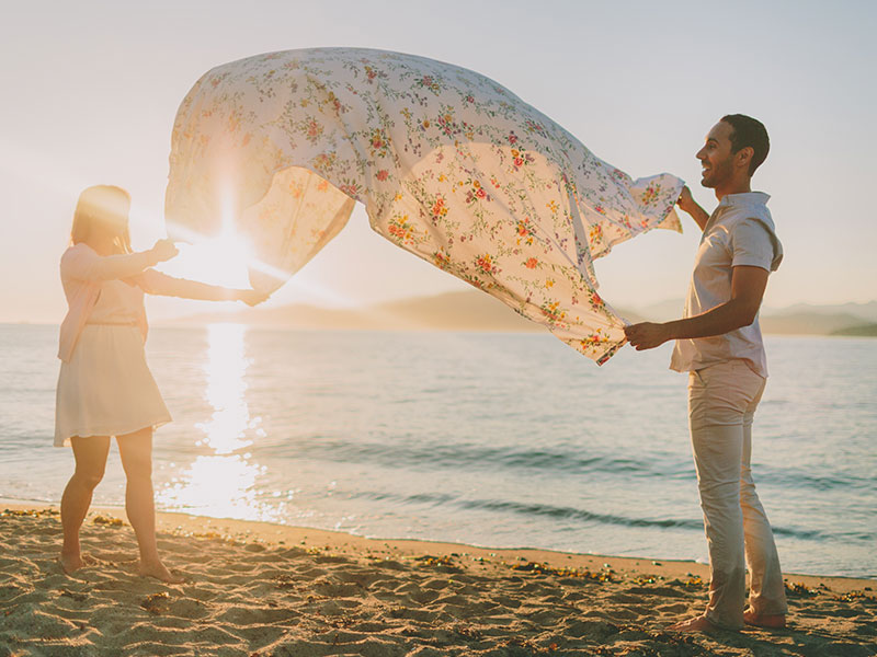 A couple using one of these unique date ideas as they spread out a picnic blanket on the beach.