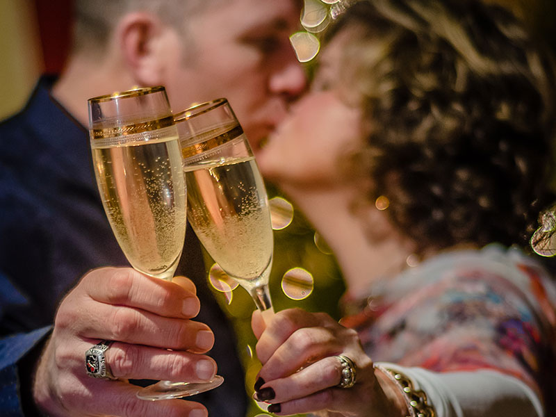 A couple who look like they epitomize these happy anniversary quotes, clinking their champagne glasses and kissing.