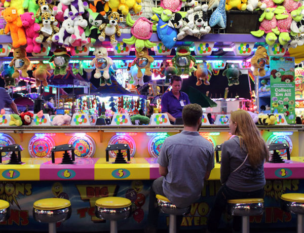 A couple trying to win a stuffed animal at the fair--one of these places to go on a date.