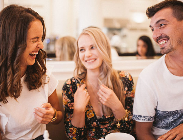 A group of friends laughing together at a table, while one of the woman is dating her friend's ex.