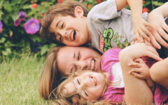 A woman who's dating a single parent with full custody laughing as she wrestles in the grass with two kids.