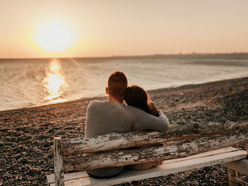 A couple who used one of these date night ideas for married couples, watching the sunset on the beach.
