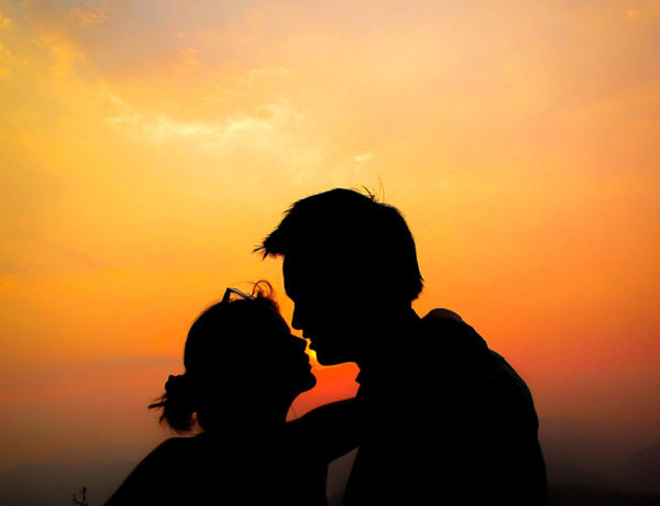 A couple in twin flame love kissing as the sun goes down.