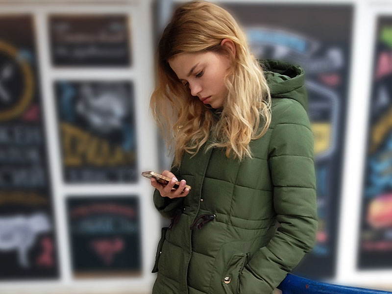As girl who isn't over her ex, checking up on him on her phone and looking unhappy.