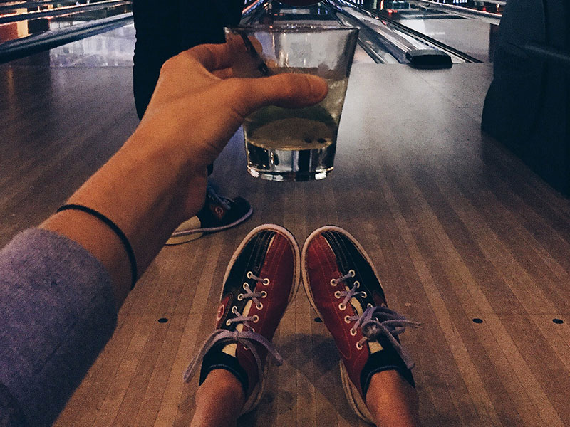 A guy drinking while bowling, using one of these indoor date ideas.