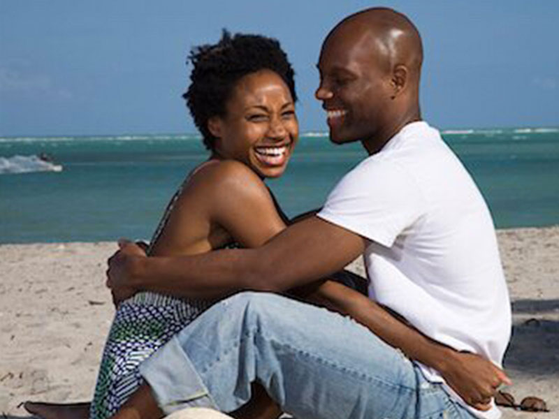 A couple over 40 dating, hugging and laughing together on the beach.